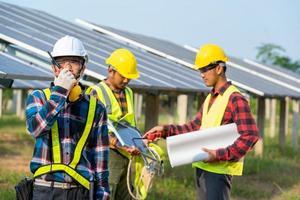 Männer, die Sicherheitsausrüstung neben Sonnenkollektoren tragen