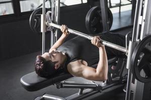 Mann auf Bankdrücken im Fitnessstudio