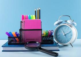 Schulmaterial und Wecker auf blauem Hintergrund