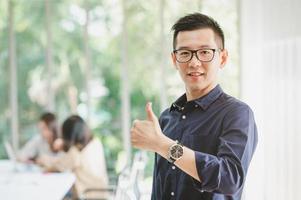asiatischer Geschäftsmann, der mit Daumen hoch Geste lächelt