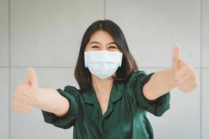 glückliche Frau, die medizinische Gesichtsmaske trägt foto