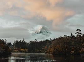 schneebedeckter Berggipfel von Wolken bedeckt foto