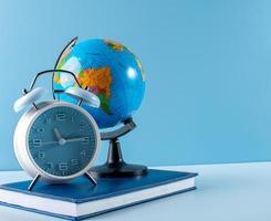 Globus, Wecker und Notizbuch auf blauem Hintergrund