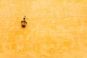 antike Lampe hängt an gelber Wand