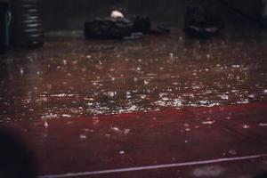 Regentropfen fallen auf Holzparkettboden