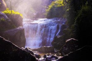 Wasserfall umgeben von Gras und Felsen