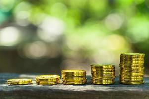 Stapel von Goldmünzen auf dem Tisch draußen foto