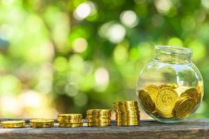 Stapel Goldmünzen und Glas auf dem Tisch draußen