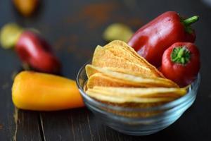 rote Chilischoten auf Kartoffelchips in der Schüssel foto