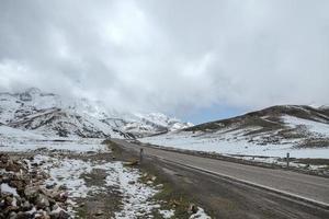 Eine leere asphaltierte Straße, umgeben von schneebedeckten Bergen mit bewölktem Himmel im hohen Atlasbereich. Marokko.