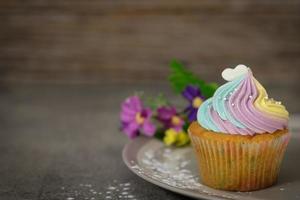 bunter Cupcake auf grauem Teller