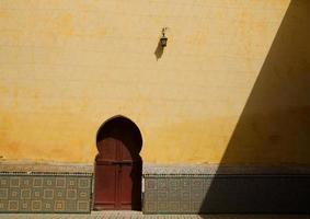 Vintage marokkanische Tür gegen gelbe Wand foto
