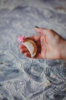 Nahaufnahme der Hand, die Empanada mit rosa Schleife darauf hält foto