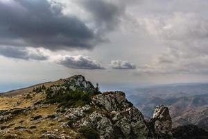 Bergfelsenklippe und bewölkter blauer Himmel foto