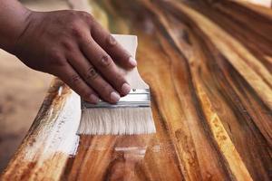 Maler mit einem Pinsel zum Lackieren von Holz foto