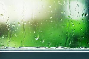 Wassertropfen strömen durch ein Glasfenster