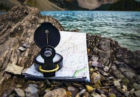 Kompass und Karte auf Felsen foto