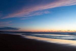 Strand und Wasser während des Sonnenuntergangs