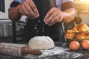 Mann streut Mehl über frischen Teig