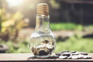 Münzen in Glasflasche mit Geld foto