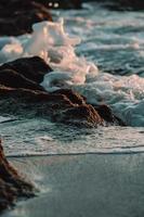 schaumiges Wasser, das auf Felsen am Strand kracht foto