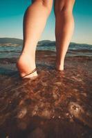zwei Beine, die im Wasser am Strand gehen