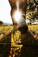 Person, die im Gras geht, das Sonne gegenübersteht foto