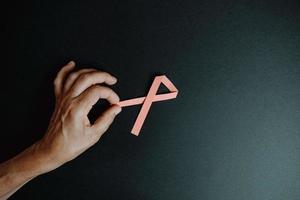 Hand, die rosa Band auf dunklem Hintergrund hält foto