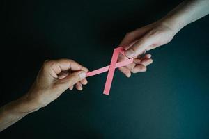 zwei Hände halten rosa Band foto