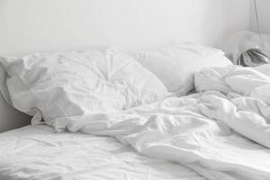 zerknittertes Bett mit weißer unordentlicher Kissendekoration im Schlafzimmer foto