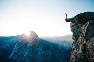 Mann, der auf Klippe am Gletscherpunkt steht foto