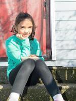 junges Mädchen, das sich hinsetzt und in Notizblock schreibt foto