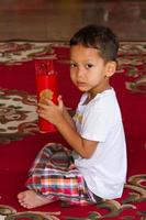 kleiner Junge schüttelt Bambuszylinder für Wahrsagerei foto