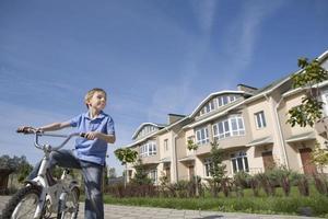 Junge steht mit Fahrrad in neuer Wohnsiedlung foto