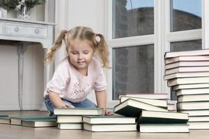 Das Kind sitzt auf dem Boden und ordnet Bücher neu. foto
