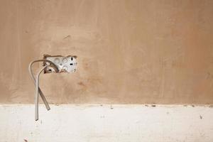 Drähte ragen aus der verputzten Wand heraus foto