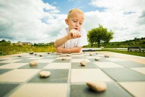 Kind spielt Entwürfe oder Dame Brettspiel im Freien foto