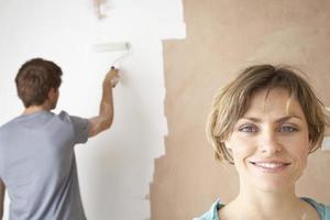 glückliche Frau mit Mann mit Farbroller an der Wand
