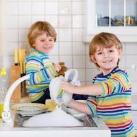 lustige Zwillingsjungen, die in der Küche beim Abwasch helfen foto