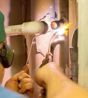 Der Klempner schweißt ein Rohr mit Gas