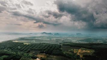 grüne Felder und Bauernhöfe unter bewölktem Himmel