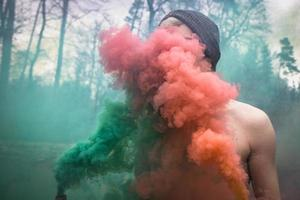 Person versteckt sich hinter rotem und grünem Rauch