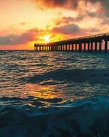Meereswellen, die an Land während des Sonnenuntergangs abstürzen