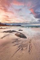 brauner Felsen an einem Sandstrand foto