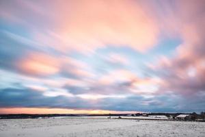 Sonnenuntergangswolken über einem kleinen Haus foto