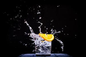 Spritzer Wasser in Glas mit geschnittener Zitrone