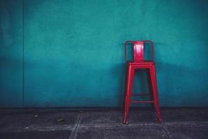 roter Metallstuhl gegen blaue Wand foto