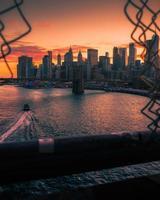 Ein Boot, das unter der Brooklyn Bridge mit der Skyline von New York City vorbeifährt
