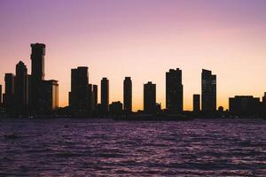 Skyline der Stadt und Wasser gegen lila Himmel