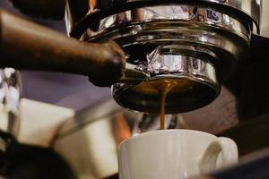 weißer Keramikbecher unter Espressomaschine